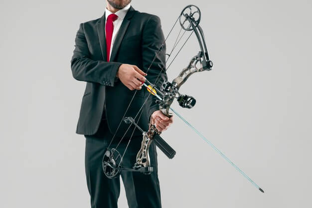 businessman aiming target with bow arrow isolated gray studio wall